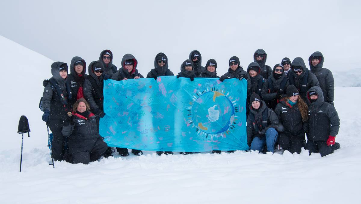 WOMEN: Some members of a Homeward Bound leadership program with a flag signed by people from all over Tasmania in Antarctica. Picture: Supplied.