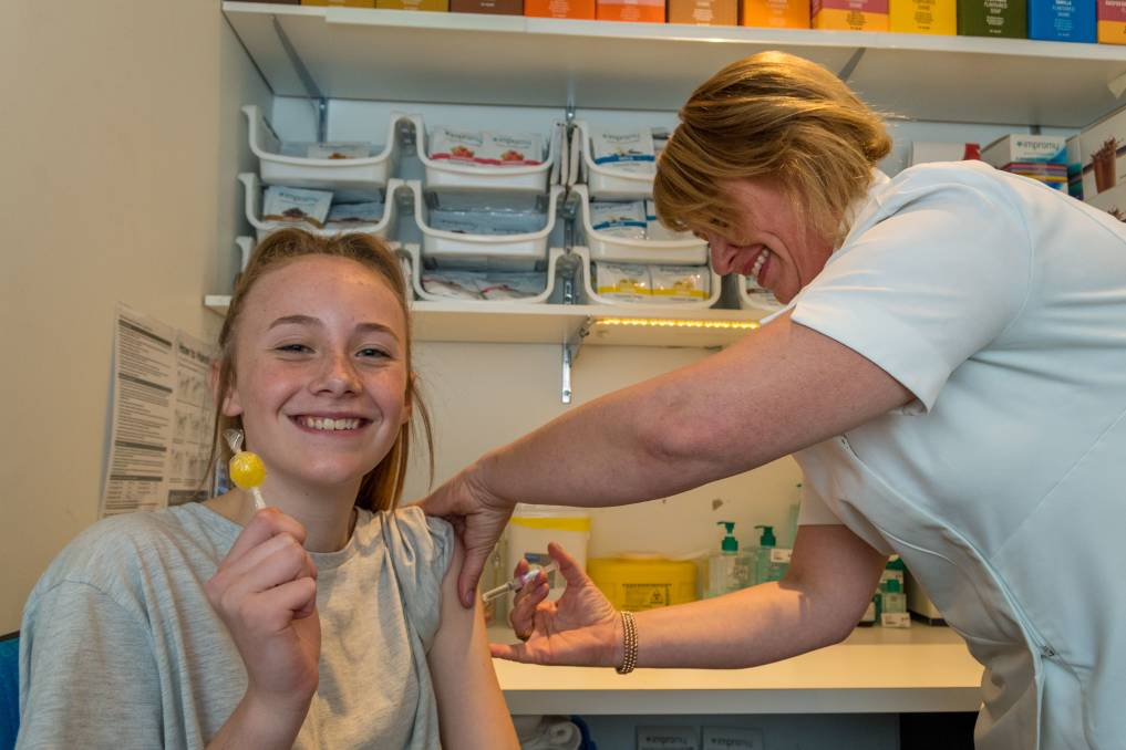 Pharmacist Tara Fox administers a flu vaccination to Loganne Fox, 13, at the Terry White pharmacy at Prospect Vale. Picture: Phillip Biggs