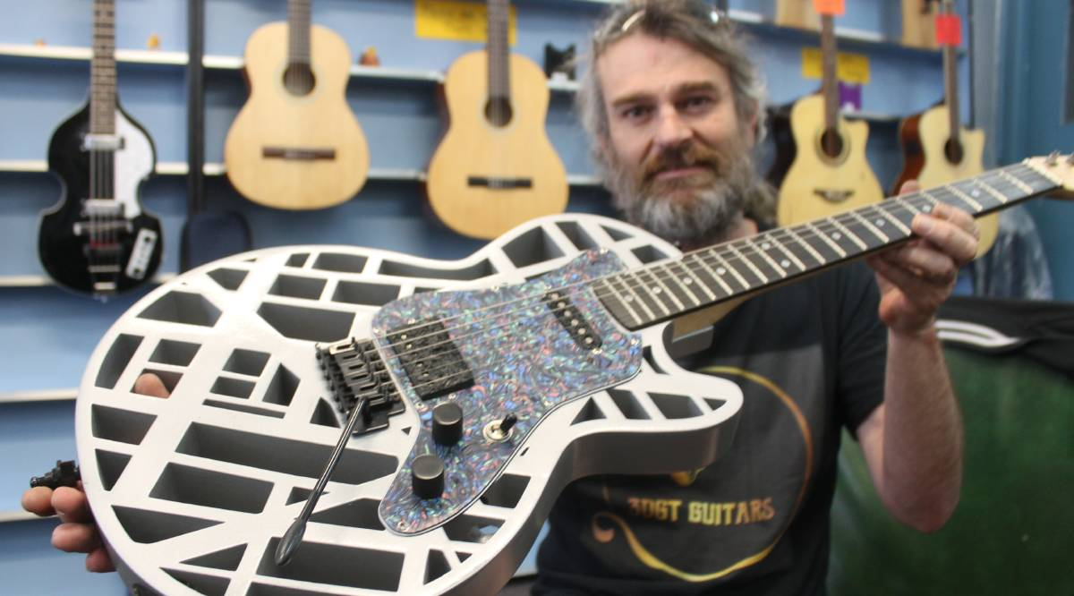 READY TO ROCK: 3DGT Guitars owner Nathan Hughston holds a guitar he designed that was made with his 3D printing technology.