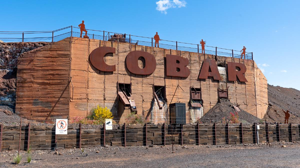 The large sign on the side of a slag heap welcomes visitors to Cobar.