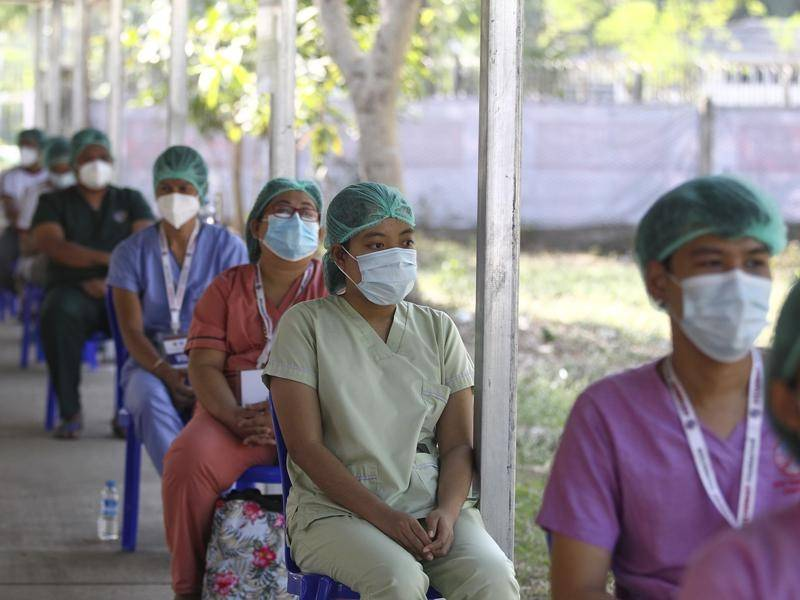 Health workers wait to receive their COVID-19 vaccine at the Ayeyarwady treatment centre in Myanmar.